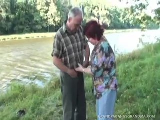 Redhead milf gives a bareback blowjob by the river