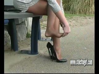 Sexy Blonde with Shapely Legs Teases in Tall Black...