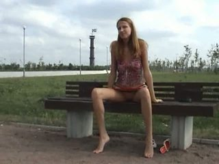 Brunette flashes tits and pussy outside on a park bench in public nudity