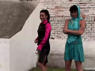 These two randy babes get tunred on by pissing in theesome outdoor